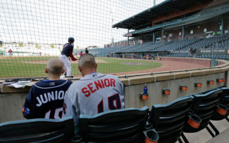 A father and son watch a Jacksonville Jumbo Shrimp game.