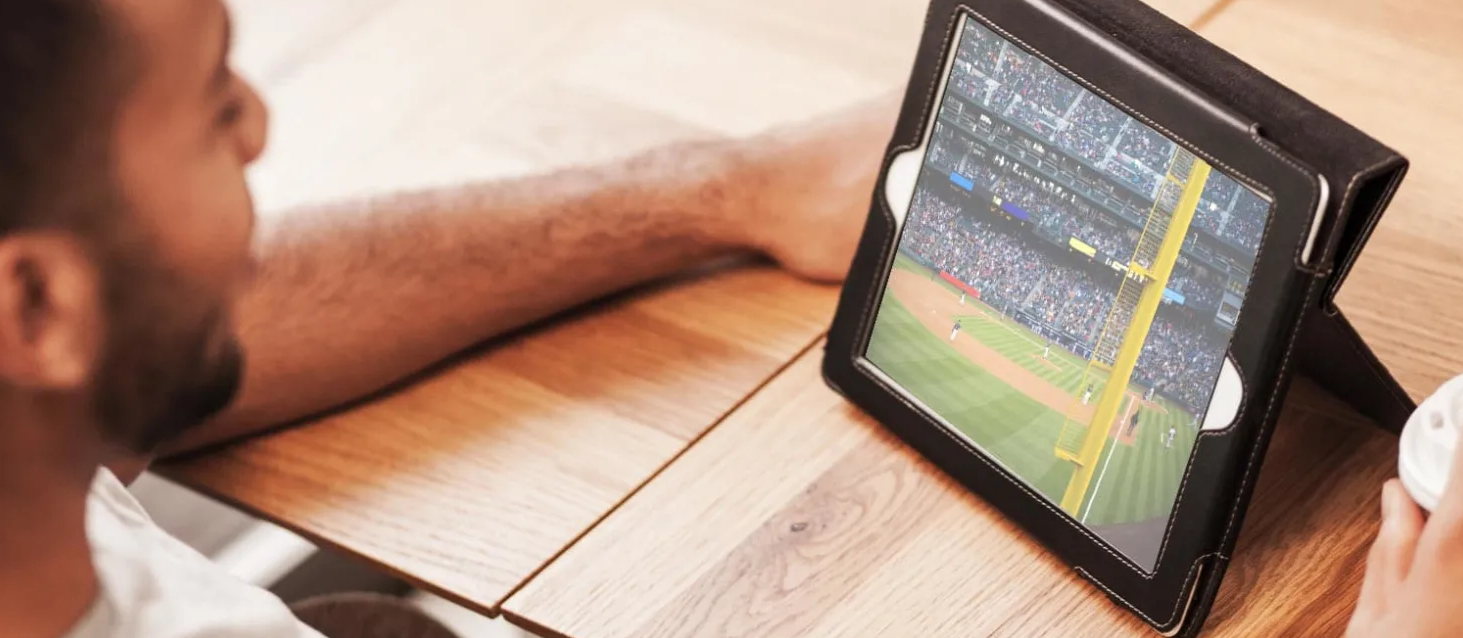 Stock image of someone watching a baseball game on their computer.