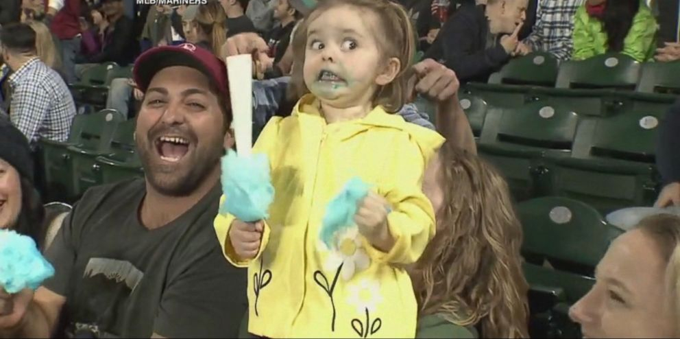A little girl enjoying cotton candy at a baseball game.